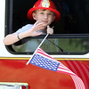 Jaxson Brothers, 9, of Townsend waves from a ladder truck in the Chelmsford 4th of July parade.  (SUN/Julia Malakie)