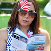 Chelmsford 4th of July parade. Kristiana Kurth of Chelmsford reads up on Nice, where she's planning a trip, while waiting for the race and parade.  (SUN/Julia Malakie)