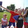 Chelmsford 4th of July parade. From left, Raeleigh Schofield, 6, of Rochester, N.H., and her stepbrother Jordan Strout, 11, his sister Isabella Strout, 9, and friend Tara Feeney, 10, all of Chelmsford, trying to stay cool with paper fans before the race and parade.  (SUN/Julia Malakie)