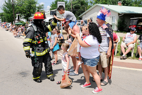 Don Knight | The Herald Bulletin<br /> A firefighter gets high fives while walking in full gear during Chesterfield's Fourth of July parade on Wednesday.