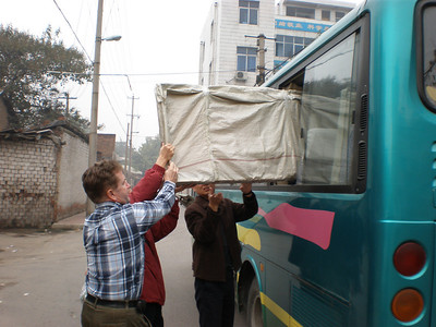 20081010_033 Packing an examination couch into the bus, prior to leaving BeiGuan hospital. We donated a cough to each of two village clinics.