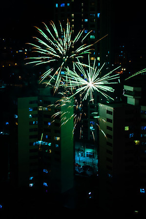 Fireworks explode dangerously close to high-rise apartment buildings.