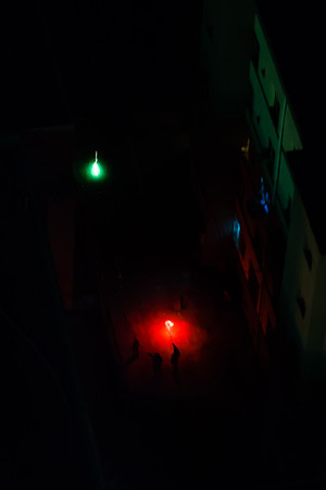Children shooting off fireworks in the courtyard of their apartment complex.