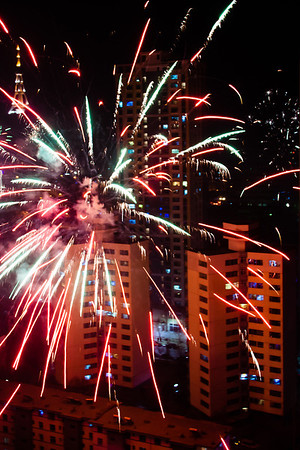 A firework explodes fifty feet in front of me, twenty-four floors up.