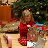 Brenna is opening presents in front of the tree