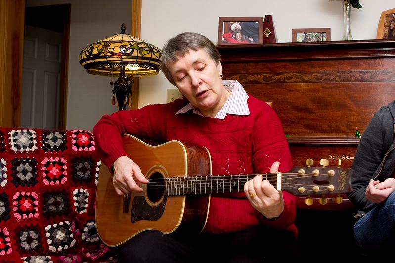 Rosewitha playing guitar and singing carols.