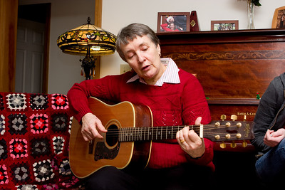 Rosewitha playing guitar and singing carols.