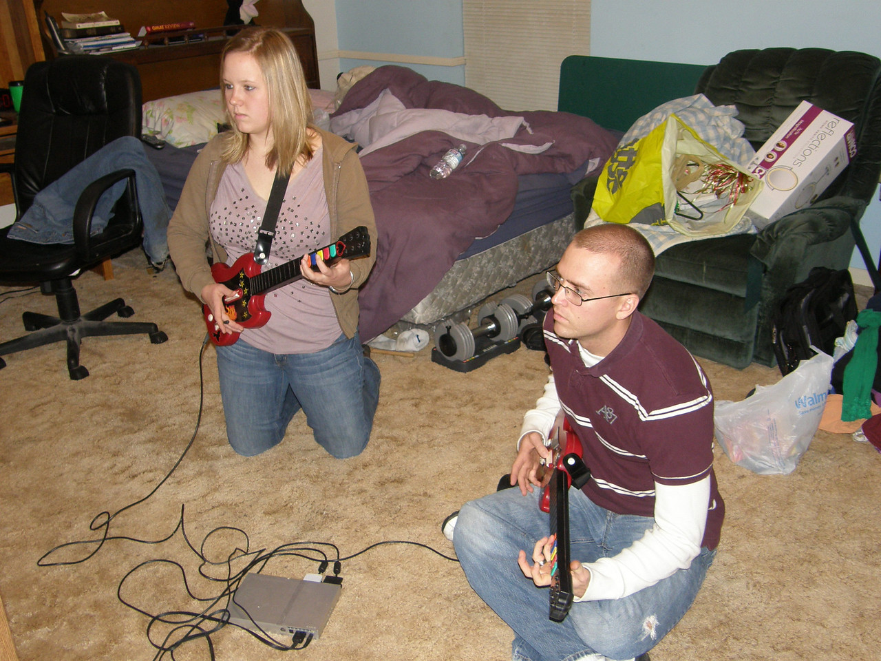 Katie and Luke intensely following the music on Guitar Hero.