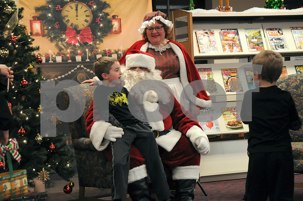-Messenger photo by Joe Sutter<br /> <br /> Grayson Chance, 7, tells Santa about his Christmas wishes while his brother, Paxton, 4, gets a candy cane after finishing his turn. The line reached out the front doors at the library with children waiting to see Santa Claus at the Lights on Central celebration Monday.