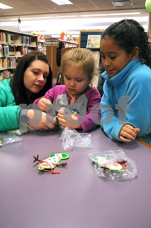 -Messenger photo by Joe Sutter<br /> <br /> Aliseya Klein, 4, gets help from her mom Amara Pommer and sister Ana Pommer, 8, creating a stocking ornament at Lights on Central. Kids also wrote letters to Santa and could check out library books Monday night.
