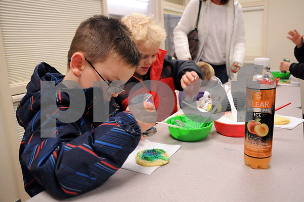 -Messenger photo by Joe Sutter<br /> <br /> Ronan Kavanaugh, 4, left, and James Kavanaugh, 5, add sprinkles to their Christmas cookies after adding some frosting at Lights on Central Monday. The cookie station proved to be a popular stop.