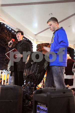 """-Messenger photo by Joe Sutter<br /> <br /> Eli Asay, a junior, and Nathan Hays, a sophomore from Fort Dodge Senior High, sing and play """"Little Drummer Boy"""" with a huge djembe at the gazebo on the city square after Santa Claus arrived Monday night. The two are in an anti-harrassment group at school called Storytellers."""