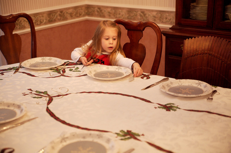 Mary placed the plates and some forks and knives.