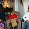 Nathan and Brady watch Alex open his present.