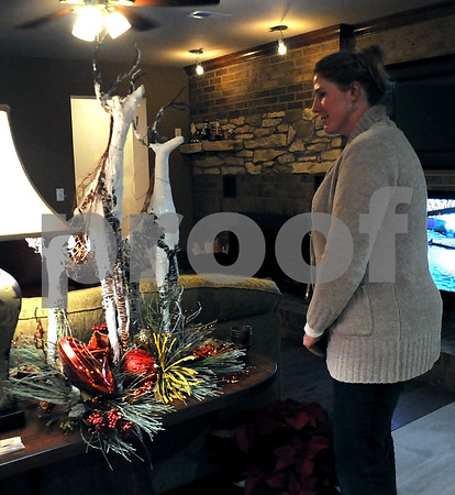 -Messenger photo by Joe Sutter<br /> <br /> Elizabeth Stanek admires the deer and pine sidepiece on display at Clyde and Dianne Knupp's home. The house was recently renovated. Stanek said she especially liked the window treatments and floral arrangements she'd seen along the Yule Walk.