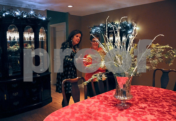 -Messenger photo by Joe Sutter<br /> <br /> MaryBeth Frischmeyer, left, and Kathy Bocken admire the centerpiece in Jim and Ann Meyer's dining room on the Fort Dodge Symphony Yule Walk Sunday evening. The home was one of four on the tour.