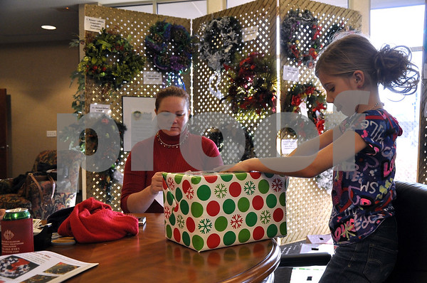 -Messenger photo by Joe Sutter<br /> <br /> Cecilia Redman unwraps a box full of names during the Gowrie Wreath Raffle. Then, helped by her mother Gayle Redman, she pulls out the name of the lucky winner of a decorated wreath. There were 44 wreaths to be given out, with the proceeds going to the Gowrie Fire Department.