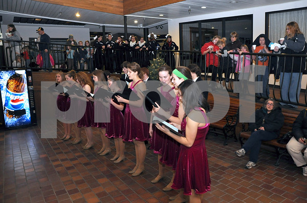 -Messenger photo by Joe Sutter<br /> <br /> The St. Edmond High School choir, directed by Nicole Brown, sing traditional Christmas carols in the lower level of the trolley center for the annual Holiday on Central event Monday night, with spectators lining up along the ramps that surround the space. Behind the choir is a gathering of some of the 50 Fort Dodge Senior High cheerleaders who volunteered at the event.