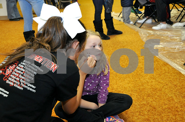 -Messenger photo by Joe Sutter<br /> <br /> Lindey Maehl, 6, gets a Santa Claus painted on her face by FDSH cheerleader Madison Fleming. Her brother Brody Maehl, 3, got a tractor drawn on his cheek. Fleming said she mostly drew Christmas trees, candy canes and snowmen Monday evening.