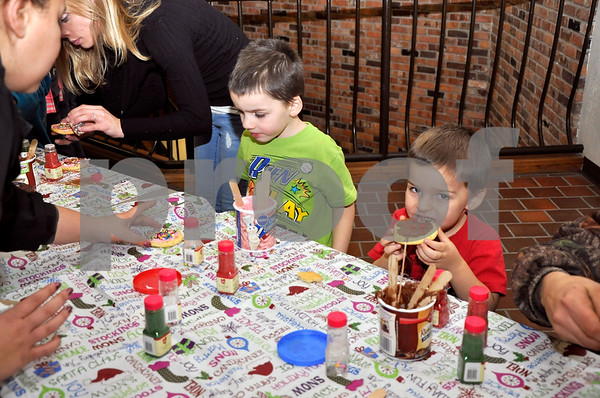 -Messenger photo by Joe Sutter<br /> <br /> Dakota Hall, 5, left, and his brother Adrian Hall, 3, take their turn at the cookie decorating table at the Holiday Lights on Central Monday night. Making cookies was one of the favorite events that evening, along with visiting Santa.