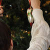 Hanging a last minute ornament on the tree.
