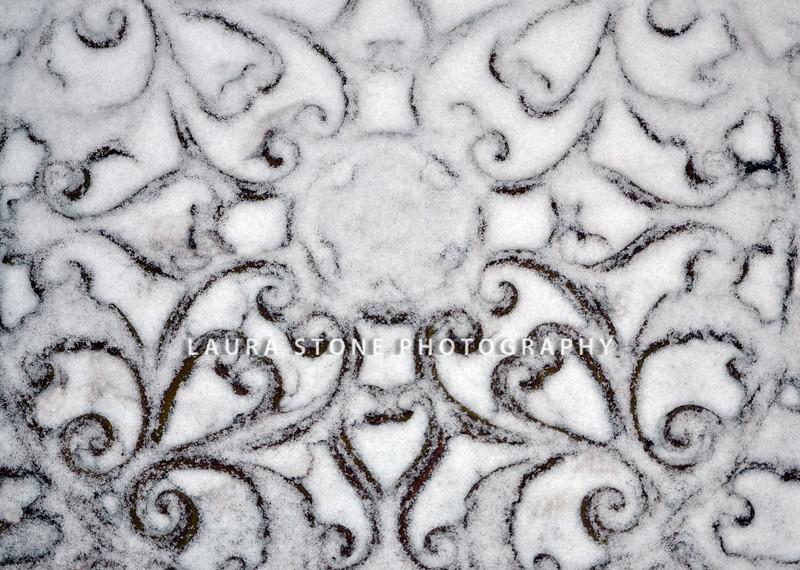 A light layer of snow on a metal door mat