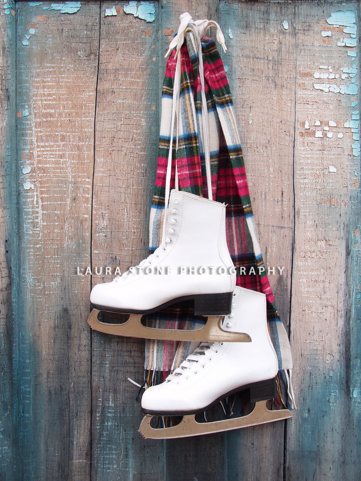 Ice Skates and a plaid scarf hanging on the side of an old barn