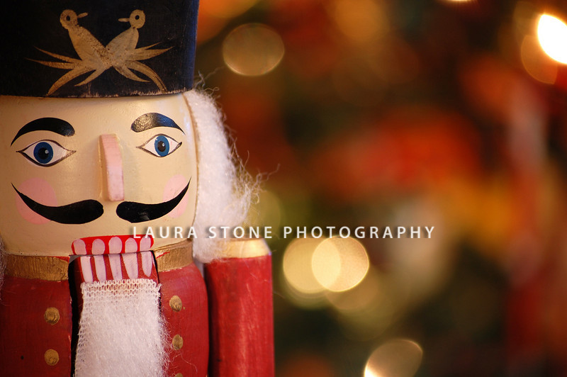 A traditional wooden nutcracker with holiday lights in the background.