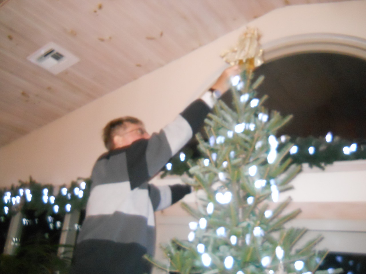Dad putting the angel on the tree