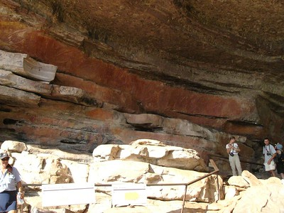 Some rock paintings are high up on inaccessible walls. Some people say that the paintings were drawn by Mimi (spirits), or with the help of spirits. Alternatively, maybe old ledges have collapsed after the paintings were drawn. Just to the left of this scene, high above the ground, is a painting of a thylacine (Tasmanian tiger). The thylacine is an extinct carnivorous marsupial, the last one dying during the twentieth century. The thylacine is thought to have disappeared from the Kakadu three thousand years ago. Incidentally, our bus driver and tour commentator can be seen on the bottom left of this photograph. As a woman, she claims the special power of being able to talk and drive at the same time!