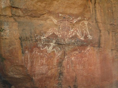 Aboriginal rock painting at Nourlangie, Kakadu National Park. This painting depicts quite a few characters and scenes. The person on the right with the tentacle-like projectings from his head is Namarrkun, 'Lightning Man'. Bright light arcs across his shoulders and he uses axes attaches to his heads, elbows and knees he strike the clouds to create thunderclaps. During the wet season, the Top End of Australia has some fearful thunder storms. Just like some people who chase tornadoes elsewhere in the world, some Australians are 'storm chasers' and go to the Northern Territory to witness the spectacle. The story of the fat looking man  in the middle of the picture is somewhat less savoury. He is Namondjok, who committed incest with a relative (perhaps not his sister, the Aborigines of the region had sophisticated relationship rules) on a ledge above this painting. Namondjok's relative took a feather from his head-dress as evidence. Namondjok stayed up on the ledge as long as he could to avoid retribution, but eventually had to come down to flee into the river. He turned into a crocodile, but not before spears were thrown into his back. Crocodiles still bear the scars of these spears today, which can be seen in the pattern of ridges on their back. Namondjok is also a creation ancestor, father of other characters in the Aboriginal dreaming.