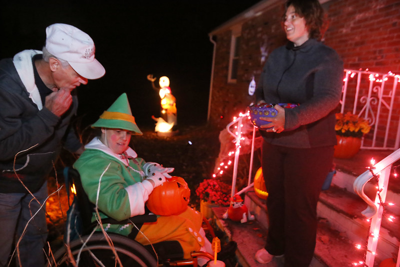 Richard Hamelin, 75, of Dracut, takes his daughter Kathy, 49, trick-or-treating for the 45th year around their neighborhood. Kathy has cerebral palsy. Marie Voulgaris of Dracut, right, hands out candy at her son's house. (SUN/Julia Malakie)