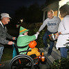 Richard Hamelin, 75, of Dracut, takes his daughter Kathy, 49, trick-or-treating for the 45th year around their neighborhood, stopping at the home of Rich and Carla Proia. Kathy has cerebral palsy. (SUN/Julia Malakie)