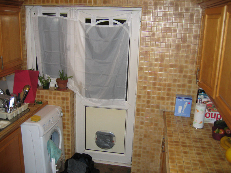 The back half of the kitchen leading to the garden. The curtains are temporary. Obviously. Note cat flap race taped shut. This is to stop the window, not because we don't love cats. We just can't eat a whole one. The first of Ty's lanudry in shot.