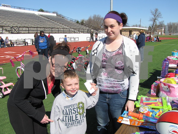 Kristina, Robert, and Jessica Johnson look over the many prizes before the Easter egg hunt began.