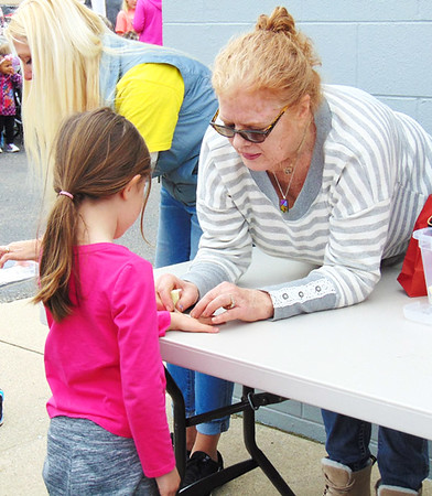 Diane Raver | The Herald-Tribune<br /> Debi Williams (right) puts a temporary Easter tattoo on Gwendolyn Freeland, 6.