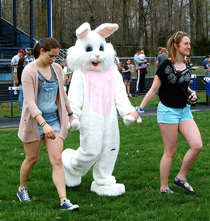Diane Raver | The Herald-Tribune<br /> The Easter Bunny receives help when walking on the football field.