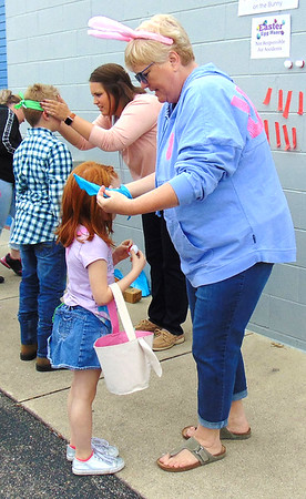 Diane Raver | The Herald-Tribune<br /> Luann Helvie adjusts the blindfold for Madelyn Saterfield, 6, at the pin the tail on the bunny station.