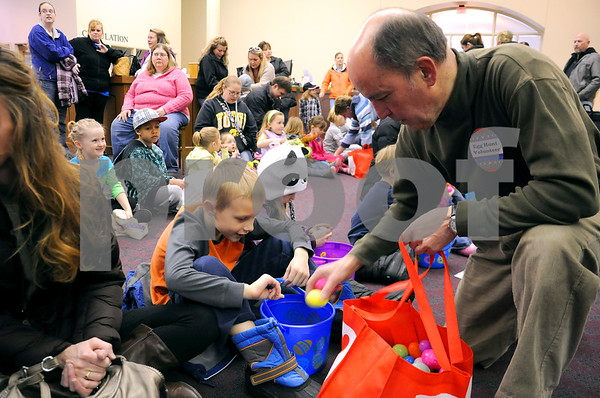 -Messenger photo by Joe Sutter<br /> <br /> Drew Sieben, retired member of the Smeltzer Charitable Trust board, hands out 12 eggs to Carter Ulland, 7. Organizers say 150 kids were in the library Saturday morning to receive eggs, candy and door prizes.