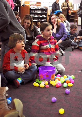 -Messenger photo by Joe Sutter<br /> <br /> Jakob Koopman, 5, and Michaela Leiting, 7, sit amidst their spoils as they listen to names being called for door prizes at the Smeltzer Family Easter Egg hunt Saturday.