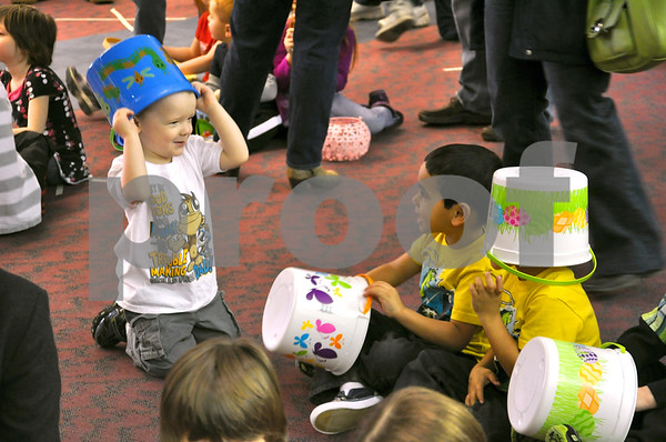 -Messenger photo by Joe Sutter<br /> <br /> Kyle Hilbert, 3, and twins Rico and Andre Roest, 4, find other uses for their egg collecting buckets while they wait for the excitement to begin.