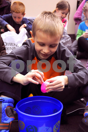 -Messenger photo by Joe Sutter  <br /> <br /> Carter Ulland, 7, peels tape off an egg to reach the candy inside.