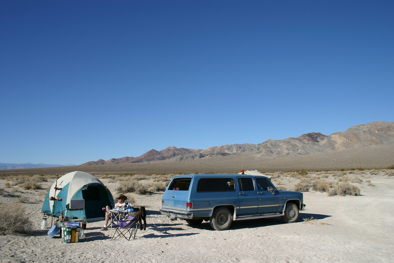 Our tent and the Suburban, with Phil lounging.