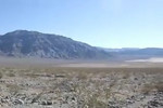 A view of about 180 degrees in Eureka Valley. Louise is walking back to camp. This panorama shows Last Chance, Saline, and Inyo Mountains.