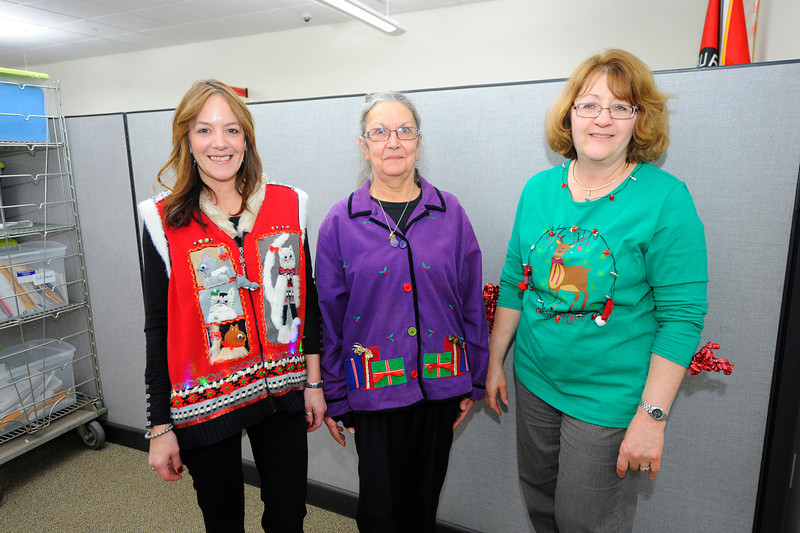 """Fitchburg City employees, from left, Jennifer Lambert who works in the treasurer's office, Tina Kreidler, who works in board of health, and Corinne Little, who works in the payroll office, pose for a photo in their """"ugly sweaters"""" for a fun holiday competition held at the Fitchburg City Office building on Boulder Dr., Thursday.<br /> SENTINEL & ENTERPRISE / BRETT CRAWFORD"""