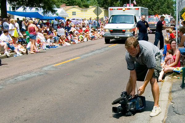 "<font size=""3"">A cameraman from a local television station is getting a low angle shot.</font>"