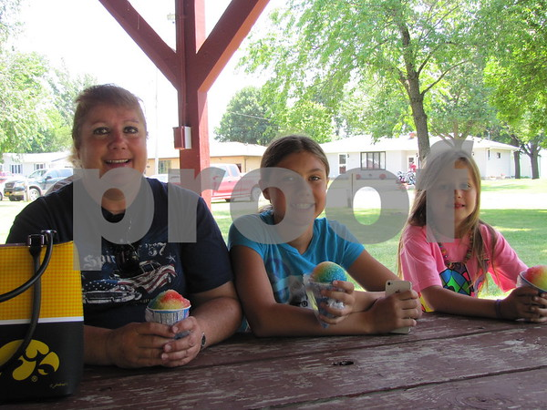 Tammy Varland, Brooke Varland, and Olivia Wall enjoyed snow cones and some shade at the Otho 4th of July festivities.