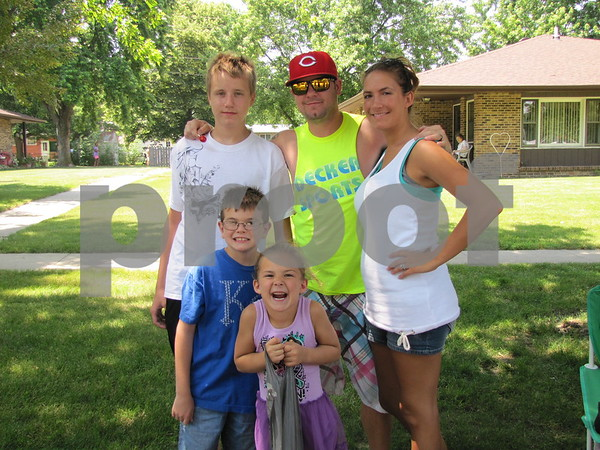 Cayden, Chris, and Heather Taylor (back) and Landon Moeller and Ava Wessels (front) after the 4th of July parade in Otho.