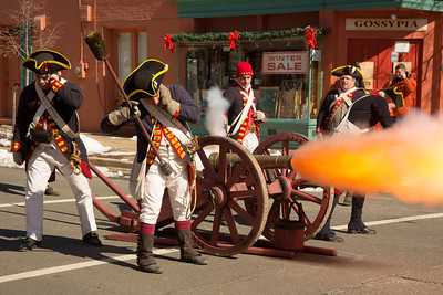 Reenactors of the First Virginia Regiment Artillery fire their cannon on Royal Street in Alexandria