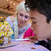 Katie Kelley from Hope Love and Magic and Marcus Clark looks closely at Petaluma Gingerbread House Showcase & Competition Hosted by Hotel Petaluma December 15-17th 2017. Victoria Webb for the Argus-Courier